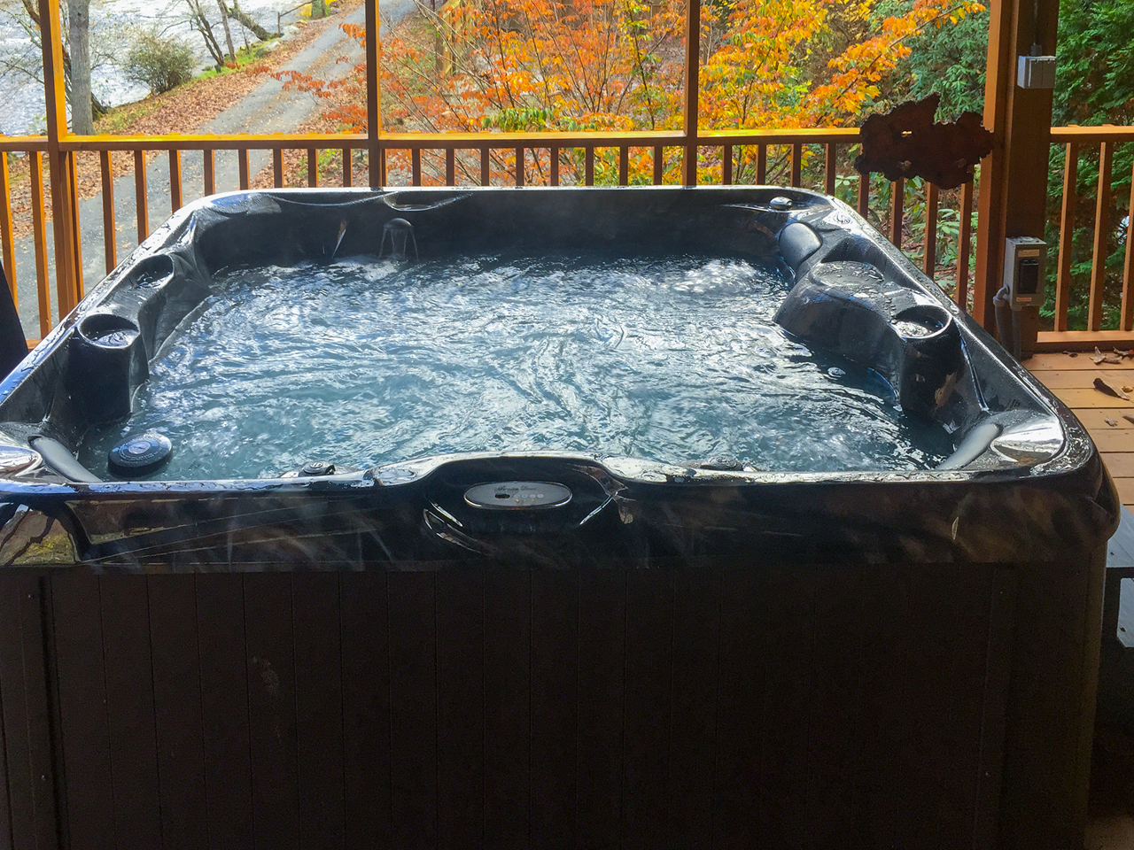 A river paradise hot tub on coverd deck overlooking tucasegee river